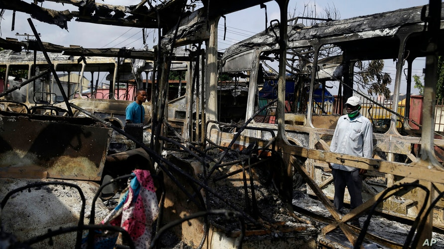 People look at burnout buses in Lagos Saturday, Oct. 24, 2020. Nigeria's president says 51 civilians have been killed in unrest…