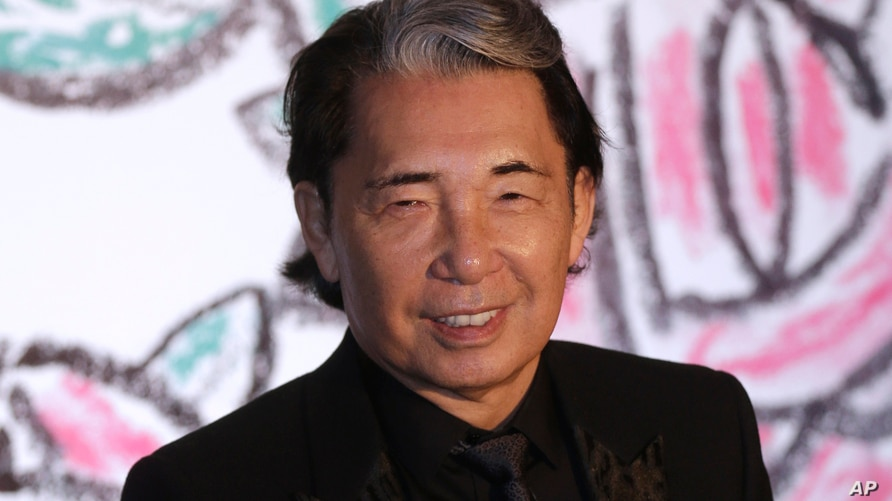 FILE - Japanese fashion designer Takada Kenzo poses for photographers as he arrives at the Rose Ball in Monaco, March 28, 2015.