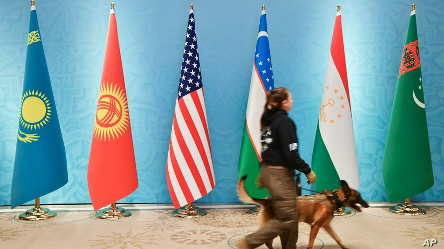 A security officer with a sniffer dog passes national flags, from left: Kazakh, Kyrgyzstan's, U.S., Uzbek, Tajikistan's and…