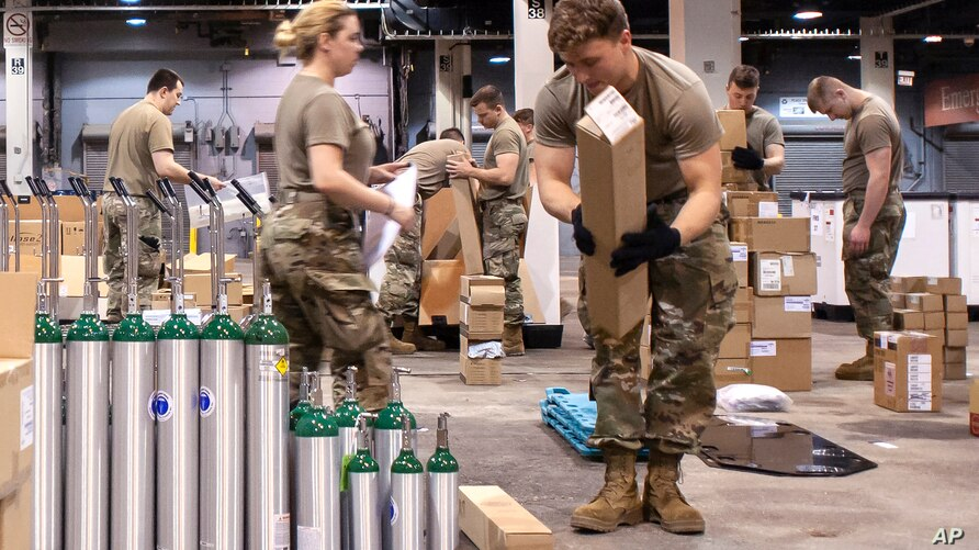 FILE - This March 30, 2020, photo provided by the Illinois Air National Guard shows members of the Guard assembling medical equipment in response to the COVID-19 coronavirus pandemic in Chicago.