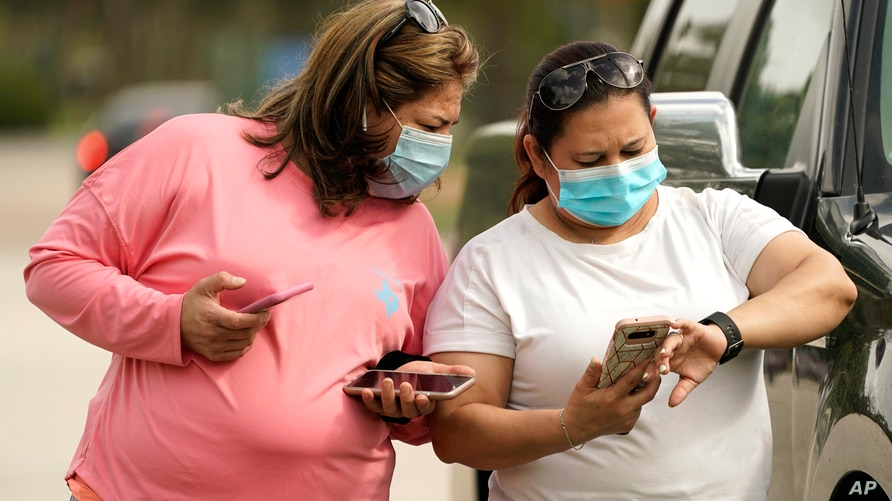 FILE -- Women wear masks as they check a mobile phone in Houston, Texas.