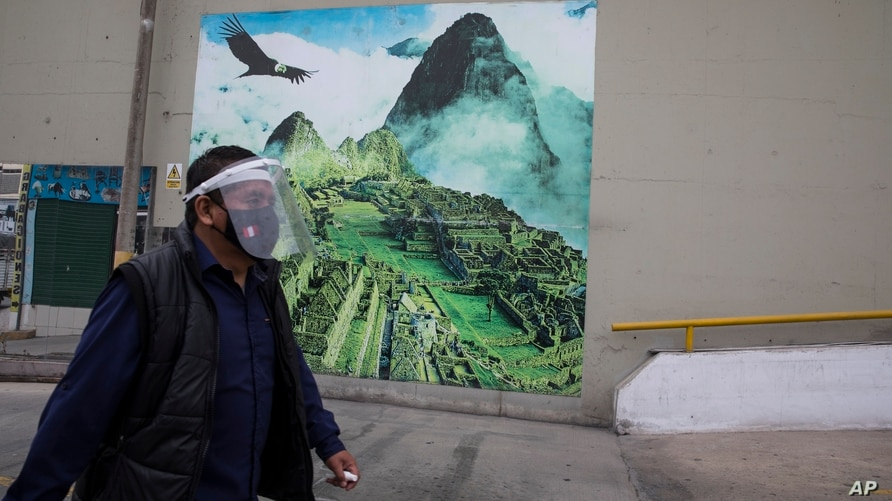 FILE - A man wearing a mask and a face shield to curb the spread of the new coronavirus walks near a mural depicting the ruins of Machu Picchu, in Lima, Peru, Sept. 10, 2020.