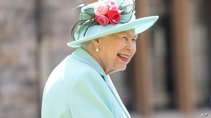 FILE - Britain's Queen Elizabeth smiles after awarding Captain Sir Thomas Moore his knighthood during a ceremony at Windsor Castle in Windsor, England, July 17, 2020.