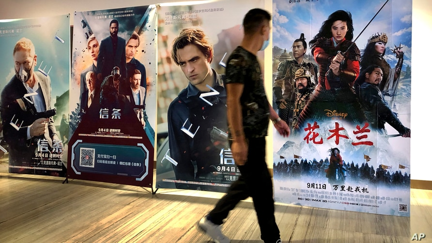 """A man wearing a face mask walks past a poster for the Disney movie """"Mulan"""" at a movie theater in Beijing, on Sept. 11, 2020."""