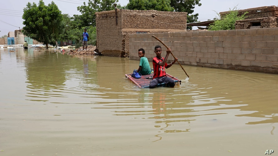 Young boys navigate a flooded street on a makeshift raft through the town of Salmaniya, about 25 miles (35 km) southwest of the…