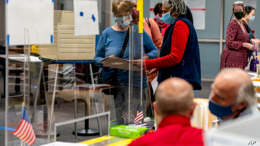 A poll worker helps a woman with her ballot in early voting at the Fairfax County Government Center, Sept. 18, 2020, in Fairfax, Virginia.