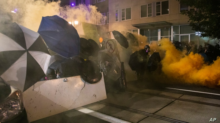 Tear gas fills the air during protests, Friday, Sept. 18, 2020, in Portland, Ore. The protests, which began over the killing of…