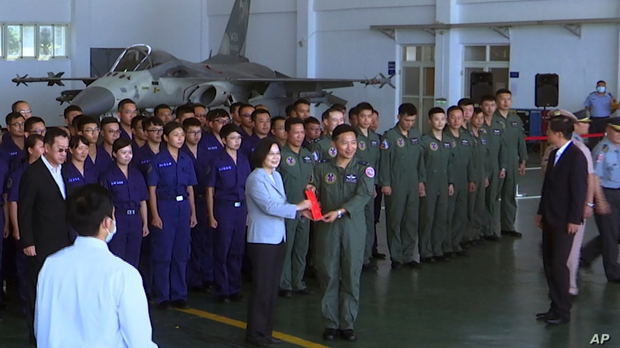 Taiwan President Tsai Ing-wen, center left, poses for photos with airmen near a Taiwan Indigenous Defense Fighter (IDF) jet…
