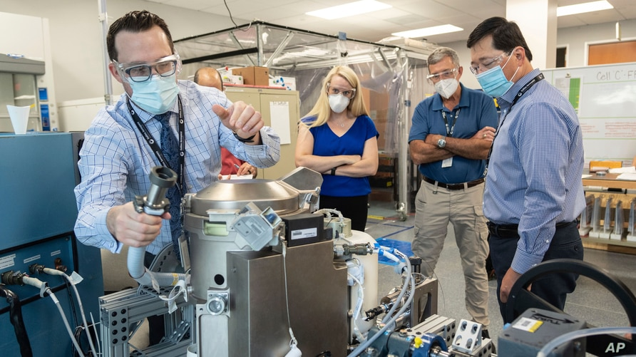 In this June 18, 2020 photo provided by NASA, astronaut Kate Rubins, center, and support personnel review the Universal Waste…