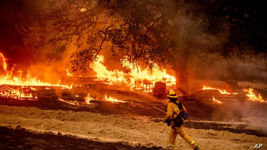 A firefighter passes flames while battling the Glass Fire in a Calistoga, California, vineyard, Oct. 1, 2020.