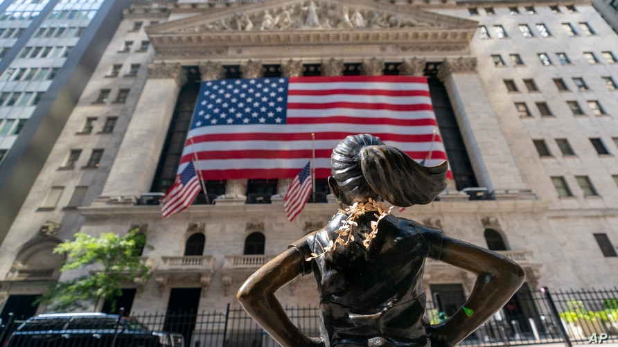 """FILE - In this Monday, Sept. 21, 2020 file photo, the """"Fearless Girl"""" bronze sculpture looks towards the New York Stock Exchange. Stocks are falling early Friday, Oct. 2 as Wall Street's first reaction to President Donald Trump's testing positive for the coronavirus was to retrench."""