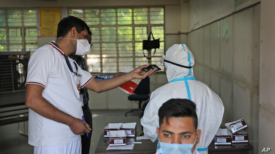 A Delhi police volunteer holds a mobile phone for a health worker as she takes an urgent call during testing for COVID-19.