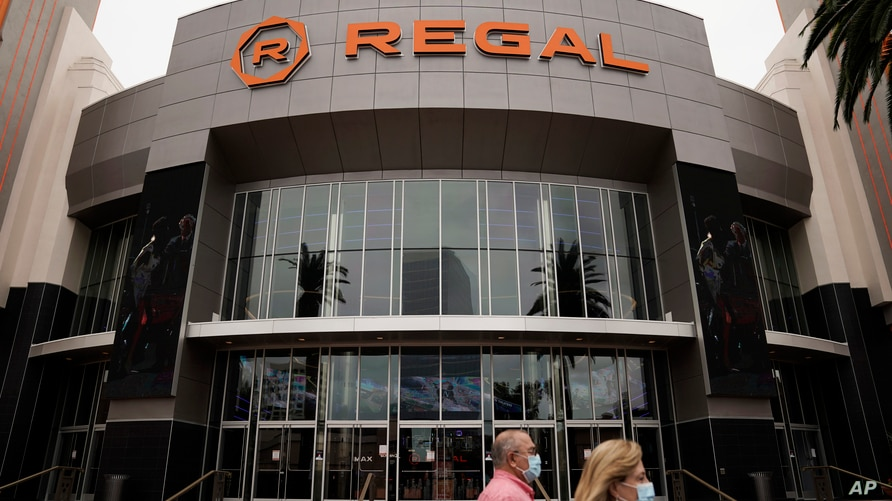 FILE - Two shoppers walk past a Regal movie theater in Irvine, Calif., on Sept. 8, 2020. The 2020 theatrical release calendar…