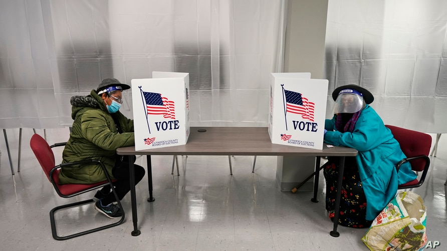 Two voters fill out ballots during early voting at the Cuyahoga County Board of Elections, Oct. 6, 2020, in Cleveland.