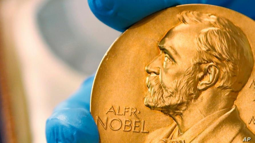 FILE - A national employee shows the gold Nobel Prize medal.