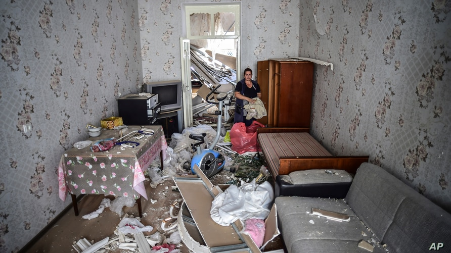 A woman stands inside her damaged house two days after shelling by Armenian's artillery during fighting over the separatist region of Nagorno-Karabakh, in Ganja, Azerbaijan, Oct. 13, 2020.
