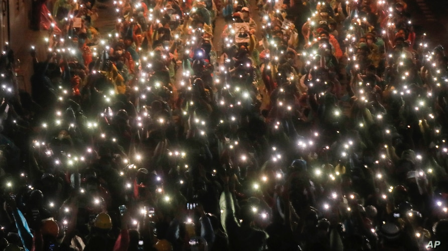 Pro-democracy protesters shine their mobile phone lights during an anti-government protest at Victory Monument during a protest in Bangkok, Thailand, Oct. 18, 2020.