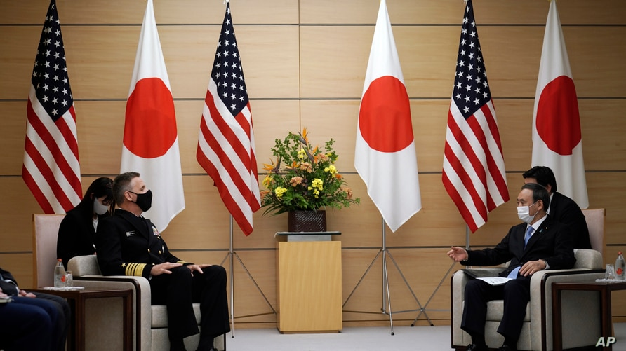 Adm. Philip Davidson, left, commander of the U.S. Indo-Pacific Command, talks with Japan's Prime Minister Yoshihide Suga during a meeting as he pays a courtesy call at the prime minister's office, Oct. 22, 2020, in Tokyo.