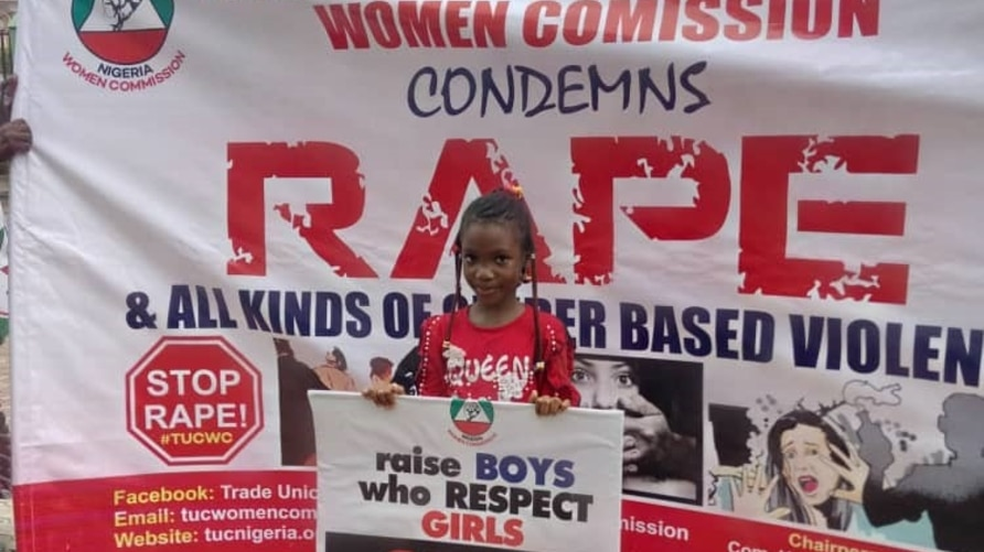 """A young girl holds a sign that says """"Raise Boys Who Respect Girls: Stop Rape."""" She stands in front a huge anti-rape banner of the Women Commission of the Nigeria Trade Union Congress."""