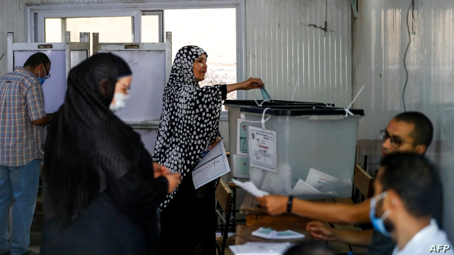 A woman arrives to vote as another casts her ballot in parliamentary elections, at a polling station in the Talibeya district of Giza, Egypt, Oct. 24, 2020.