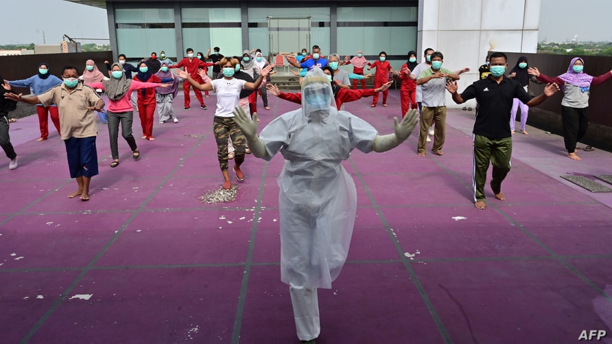 A gymnastics instructor wearing personal protective equipment (PPE) leads a morning exercise for patients of the COVID-19 coronavirus at a hotel designated to treat asymptomatic patients in Karawaci, Indonesia's Banten province.