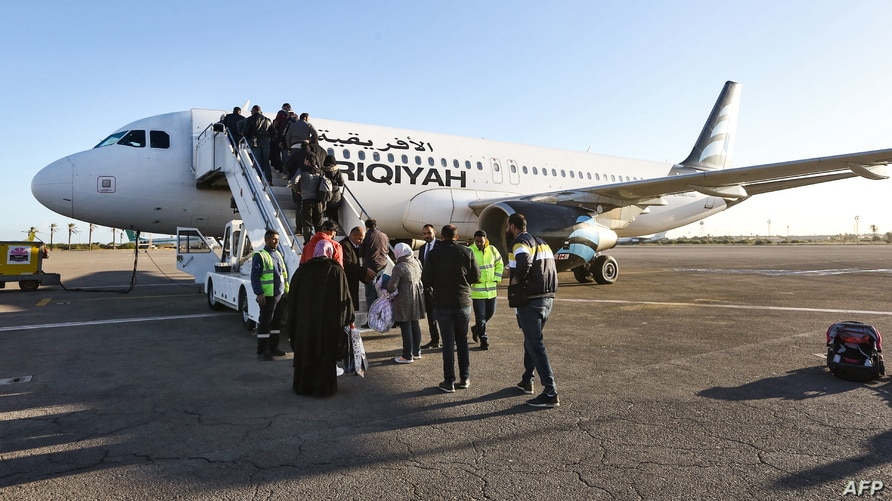 FILE - Passengers board an airplane at Mitiga International Airport, east of the Libyan capital Tripoli, December 12, 2019.