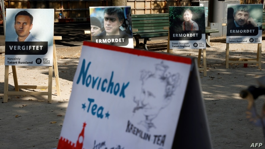 """FILE - A poster showing Russian opposition leader Alexei Navalny (L) with the word """"poisoned"""" and a mock offering of """"Novichok Tea"""" are seen outside the Russian embassy in Berlin, Germany, during a protest, Sept. 23, 2020."""