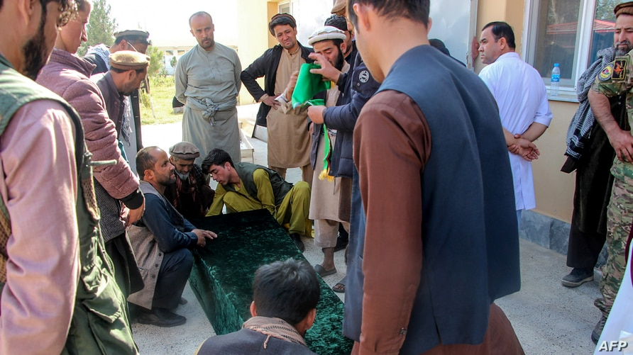 Relatives and others gather around the coffin of a soldier who died in heavy fighting between Afghan security and Taliban forces, outside a hospital in Takhar province, Oct. 21, 2020. Nearly a dozen chidren were killed in an airstrike a day later.
