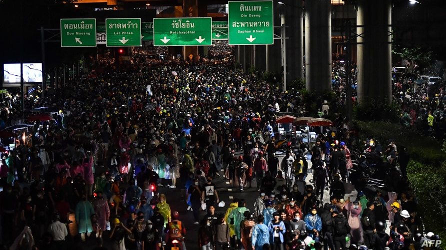 Protesters walk along a road during an anti-government rally at the Lat Phrao intersection in Bangkok, Thailand, Oct. 17, 2020, as they continue to defy an emergency decree banning mass gatherings.