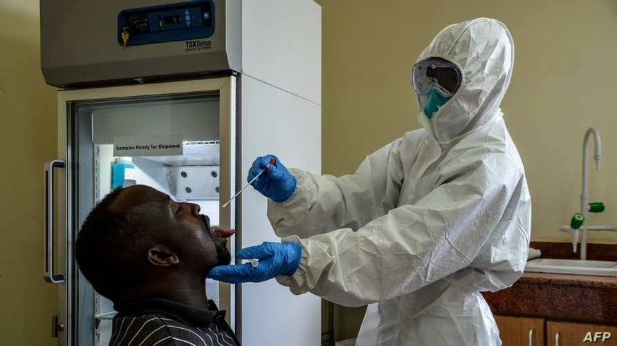 FILE - An Ugandan health worker takes samples to test a truck driver for the coronavirus, at the Malaba Border Post in Malaba, on the border with Kenya, Uganda, April 29, 2020.