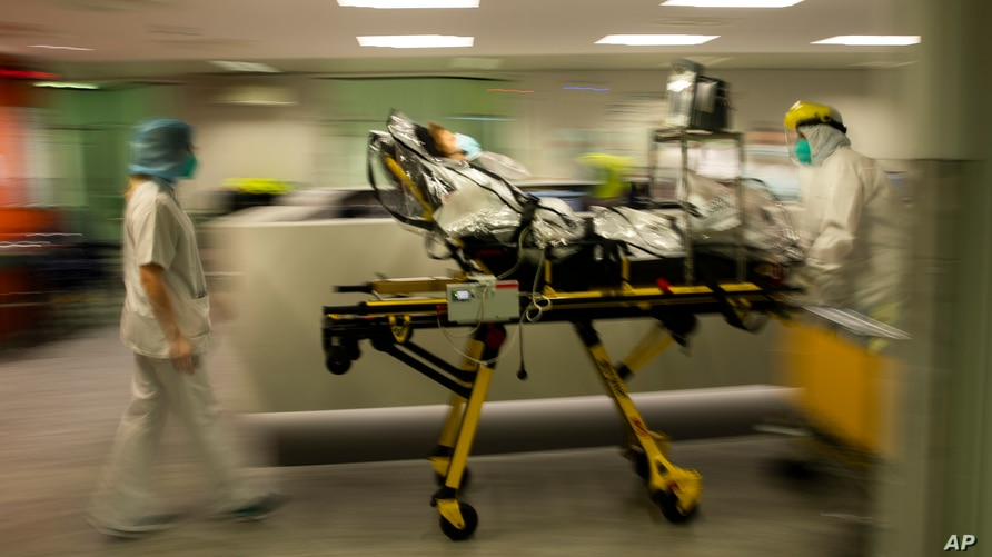 FILE - Medical staff move a COVID-19 patient at the CHR Citadelle hospital in Liege, Belgium, Oct. 21, 2020.