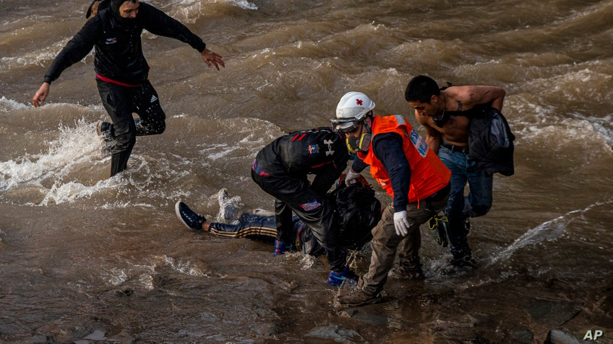 Paramedics and demostrators attend a youth who fell into the Mapocho river from a bridge during a police charge on protesters in Santiago, Chile, Oct.2, 2020.