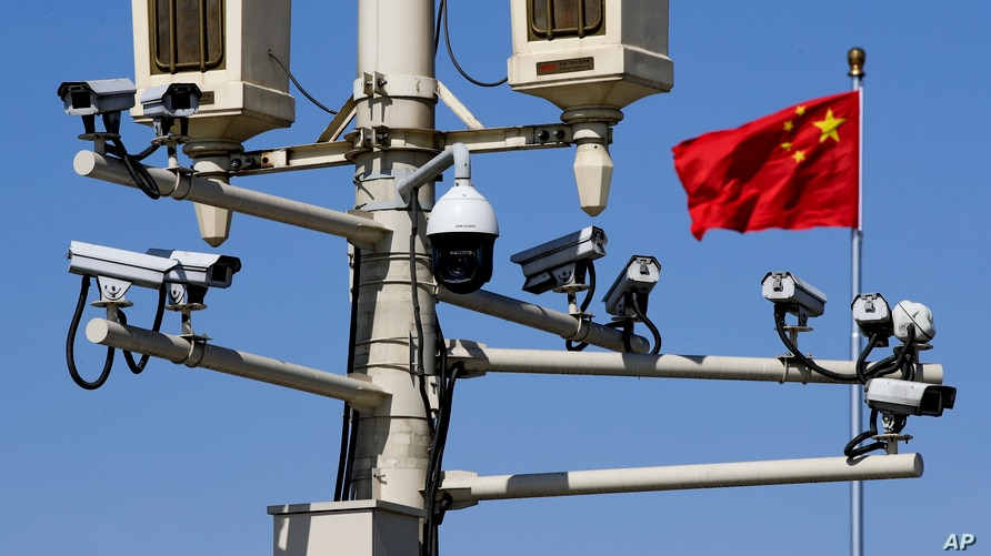 FILE - A Chinese national flag flutters near surveillance cameras mounted on a lamp post in Tiananmen Square in Beijing, China, March 15, 2019.