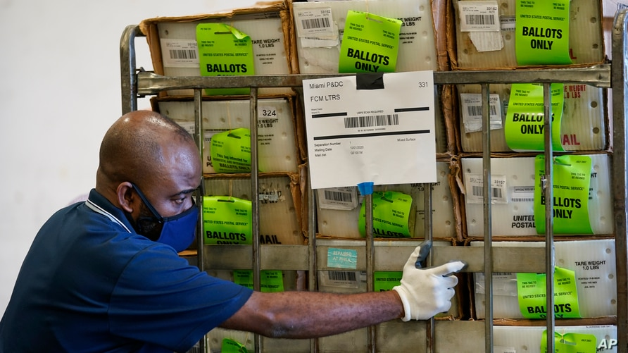 A Miami-Dade County Elections Department employee loads a cart of vote-by-mail ballots into a truck for transport to a local U.S. Postal Service office, Oct. 1, 2020, in Doral, Florida.