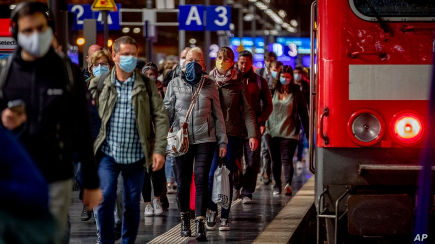 Passengers wear face masks as they leave a train in the central train station in Frankfurt, Germany, Oct. 8, 2020.