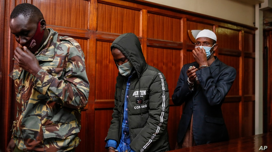 Hussein Hassan Mustafah, center, and Mohamed Ahmed Abdi, right, who were both found guilty of supporting the gunmen involved in the Westgate Mall attack in Sept. 2013, leave the Milimani court in Nairobi, Kenya, Oct. 7, 2020.