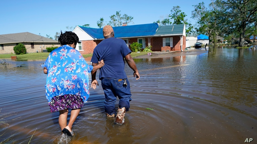 Soncia King and her husband Patrick King in Lake Charles, La., walk through the flooded street to their home, Oct. 10, 2020, after Hurricane Delta moved through on Friday.
