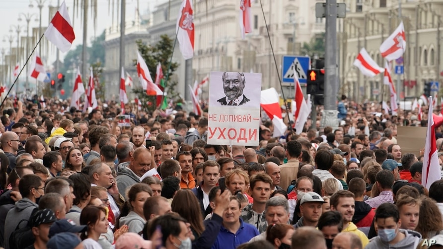 "FILE - Belarusian opposition supporters carry old Belarusian flags and a poster with a portrait of Belarusian President Alexander Lukashenko reading ""Go away,"" at a rally at Independence Square in Minsk, Belarus, Aug. 23, 2020."