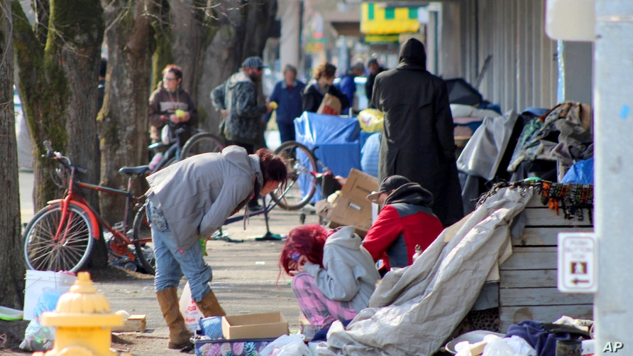 FILE - Homeless people crowd a sidewalk in downtown Salem, Oregon, March 3, 2020. A $20 billion funding effort by the Trump administration aims to support providers of mental health and substance abuse services during the coronavirus pandemic.