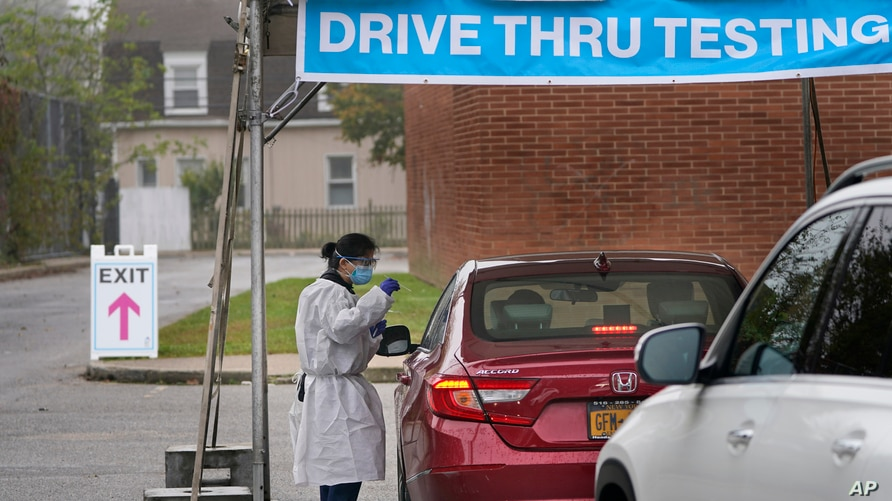 FILE - Medical personnel prepare to administer a COVID-19 swab at a drive-through testing site in Lawrence, New York, Oct. 21, 2020.