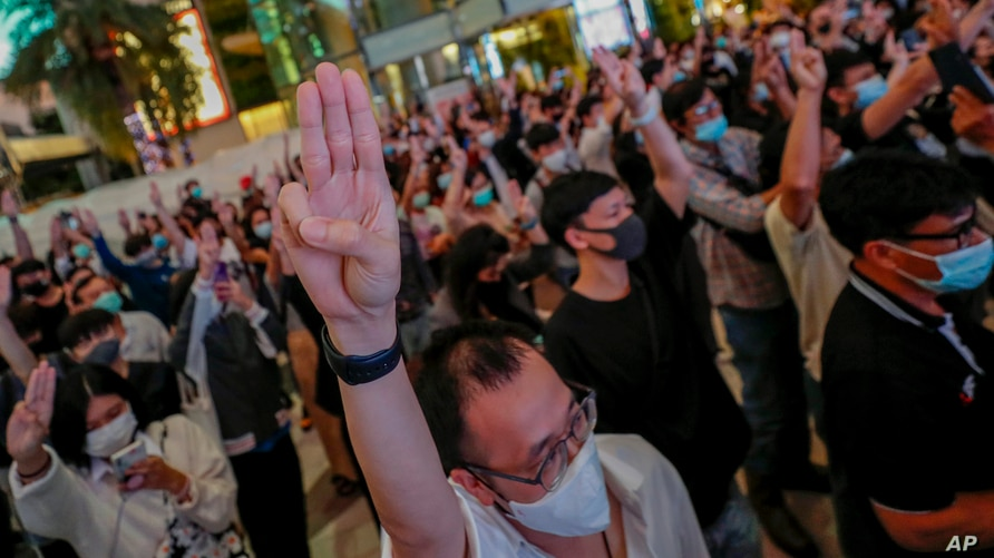 Pro-democracy activists flash three-fingered salute while listening to the national anthem outside Siam Paragon, one of the largest shopping malls, in Bangkok, Thailand, Oct. 20, 2020.