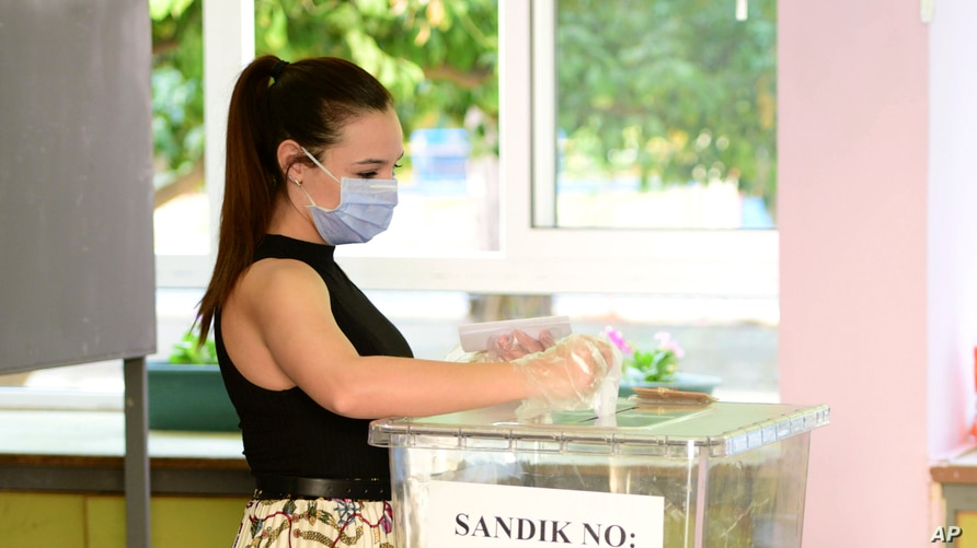 A woman casts her ballot at a polling station during the Turkish Cypriots election in Nicosia, Cyprus, Oct. 11, 2020.