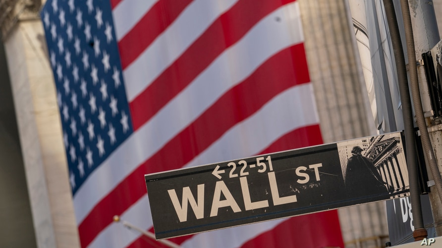 FILE - A Wall Street sign is seen against the background of a giant American flag hanging on the building of the New York Stock Exchange, in New York City, Sept. 21, 2020.