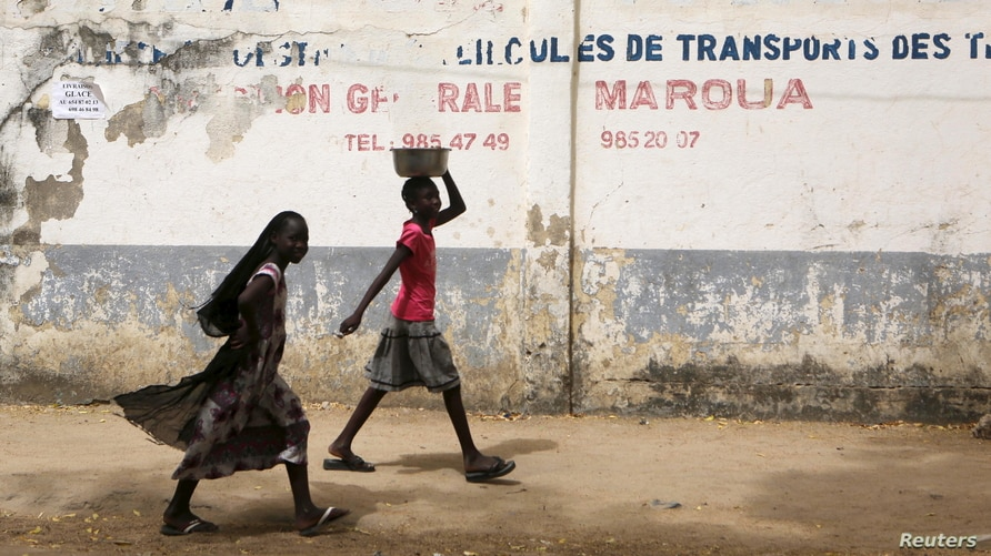 FILE - Girls walk on a road in Maroua, Cameroon, March 17, 2016. Amid misconceptions and skepticism surrounding HPV vaccinations in the country,efforts are underway to educate parents about the importance of having girls vaccinated.