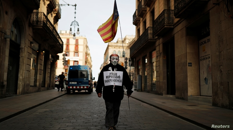 """A man wearing a Guy Fawkes mask holds an Estelada, a Catalan pro-independence flag, as he walks towards a protest against a separatism-related police operation, in Barcelona, Spain, Oct. 28, 2020. His signs oreads """"Enough repression. Independence."""""""