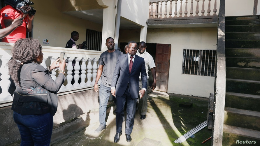 FILE - Maurice Kamto, leader of the Cameroon Renaissance Movement, walks out after a news conference in Yaounde, Cameroon, Oct. 8, 2018. A U.N. report accuses the Cameroon government of stifling him and his movement.