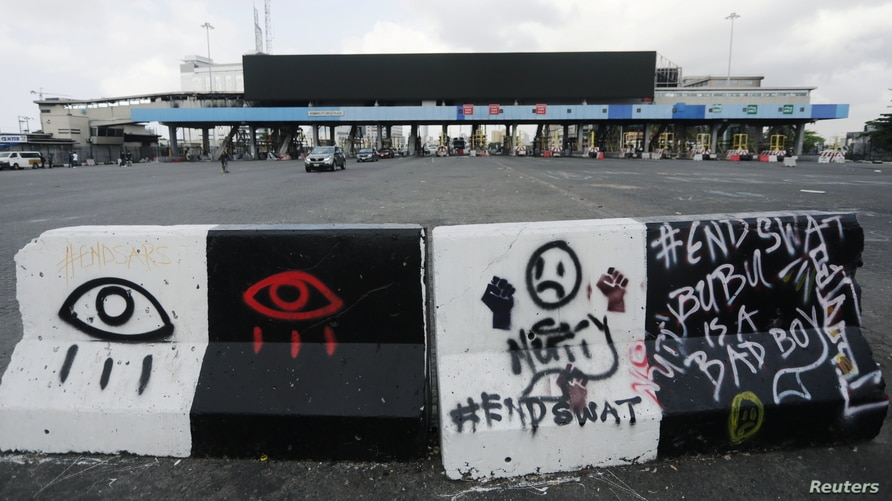 A road block with graffiti is seen at the Lekki toll gate, site of protests that turned deadly when security forces opened fire on demonstrators earlier this week, in Lagos, Nigeria, Oct. 24, 2020.