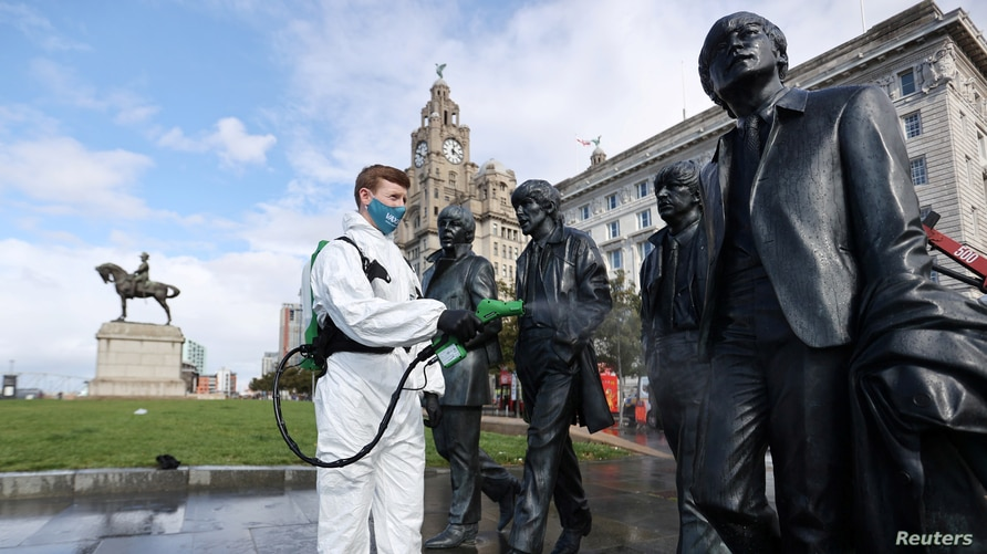 A worker disinfects a statue of the Beatles amid the coronavirus pandemic, in Liverpool, Britain, Oct. 1, 2020.