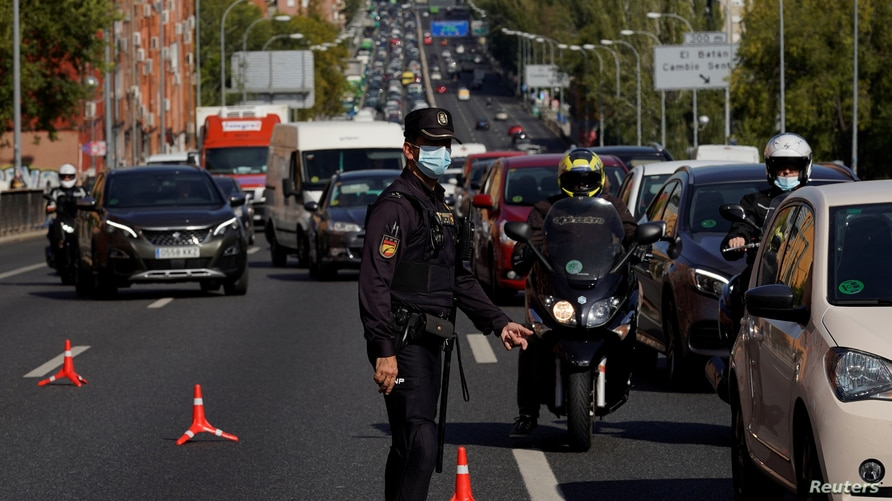 A police officer wearing a protective mask stands at a traffic checkpoint during a partial lockdown amid the coronavirus pandemic, in Madrid, Spain Oct. 9, 2020.