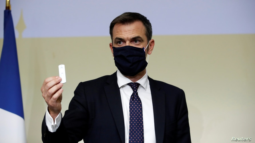 FILE - French Health Minister Olivier Veran, wearing a protective face mask, holds a COVID test during a news conference at Bichat hospital in Paris, France, Oct. 1, 2020. Veran's home was among those searched as part of a COVID response probe.